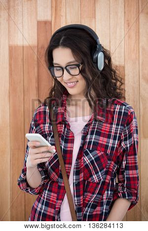 Hipster with headphones and smartphone on wooden background