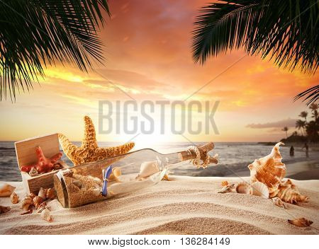 Sandy tropical beach with shells, bottle with message and starfish in beautiful sunset light