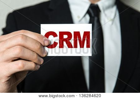 Business man holding a card with the text: CRM