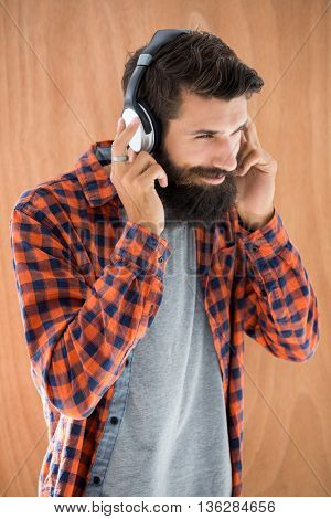 Hipster listening to music on wooden background