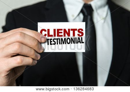 Business man holding a card with the text: Clients Testimonial