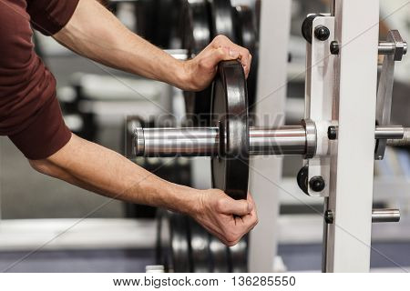 Male hand putting weight plate on barbell. Weightlifting training preparation. Weight plate in strong hand of fitness instructor in gym closeup