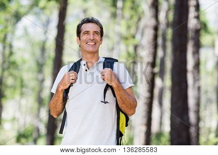 Man smiling and posing with his backpack on the wood