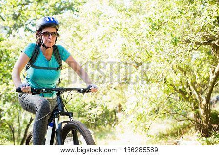 Mature woman riding bike on the wood