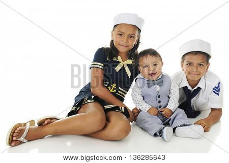 Three siblings happily sitting together in their sailor outfits.  On a white background with plenty of space for your text on the upper left.