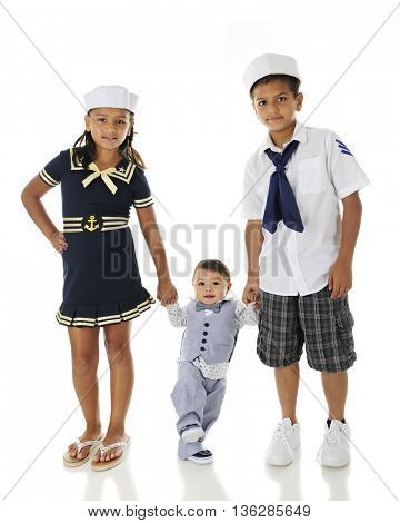 Two Hispanic siblings helping their baby brother walk.  All are dressed in sailor outfits.  On a white background.