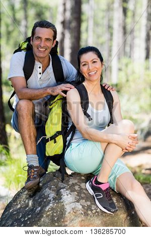 Couple smiling and posing on a rock