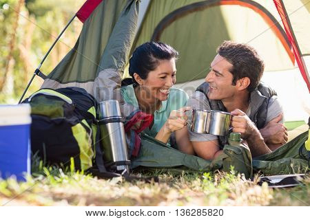 Couple laying and clinking cup on their tent