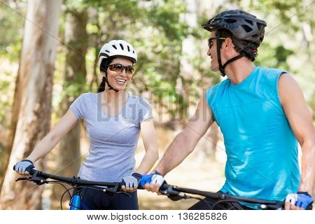Couple looking each other with their bikes on the wood