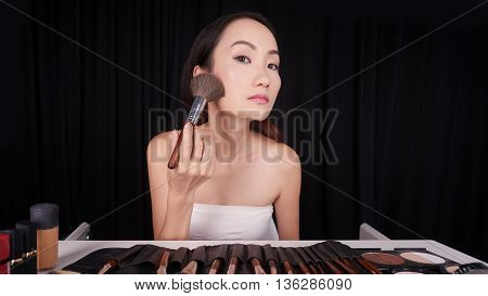Pretty Chinese woman applying face powder with brush