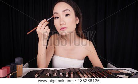 Pretty Asian woman applying eyeshadow in front of mirror