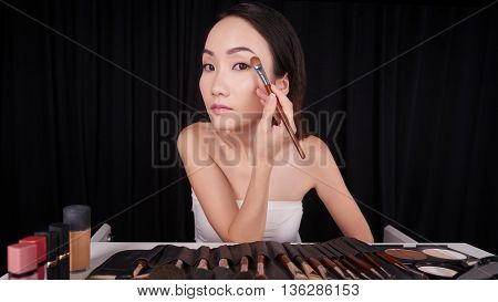 Young Chinese lady getting ready at her vanity