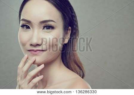 Face of smiling Chinese woman with flawless make-up