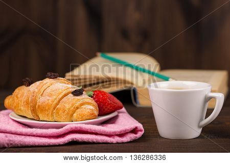 cup of coffee and a croissant and book