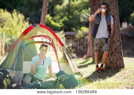 Couple posing and holding cup on camp site