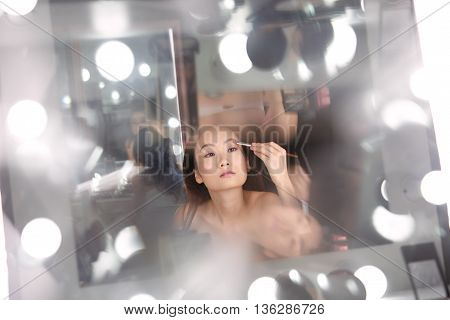 Pretty Asian girl doing make-up at her vanity