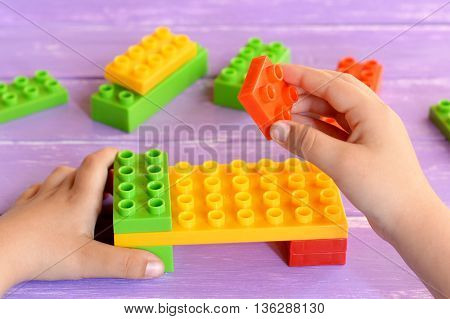 Child holds the building blocks toys in his hands and makes the bed. Building blocks toys for children on lilac wooden background. Kids activity in kindergarten or at home