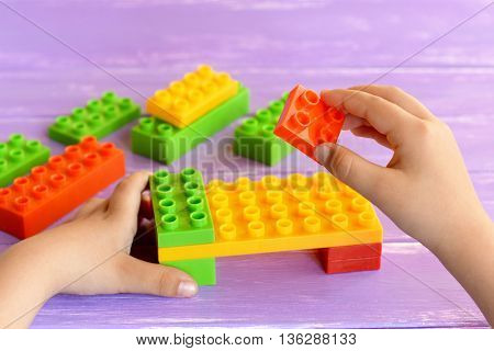Little child holds a designer blocks in his hands and does bed toy. Colored plastic constructor on lilac background. Toy building blocks into game. Child masters fine motor skills