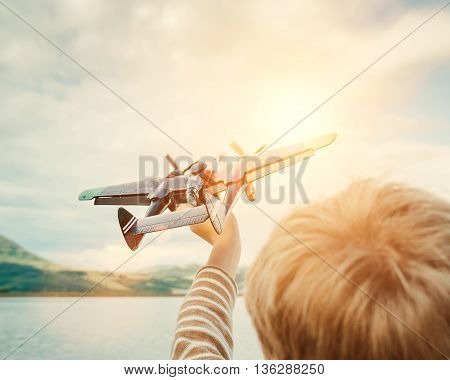 Child's hand with toy plane on the sunny background