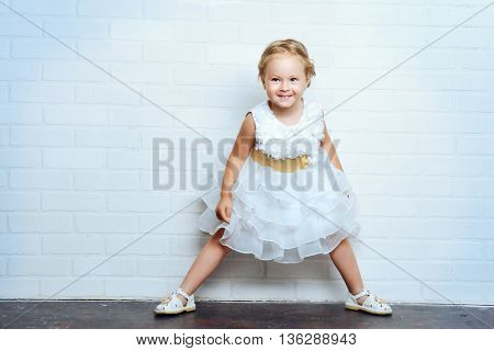 Angelic little girl in a beautiful white dress standing by the white brick wall. Childhood.