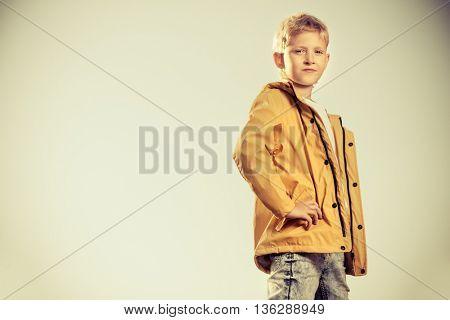 Cool modern eight-year boy posing on a sky background. Kid's fashion.