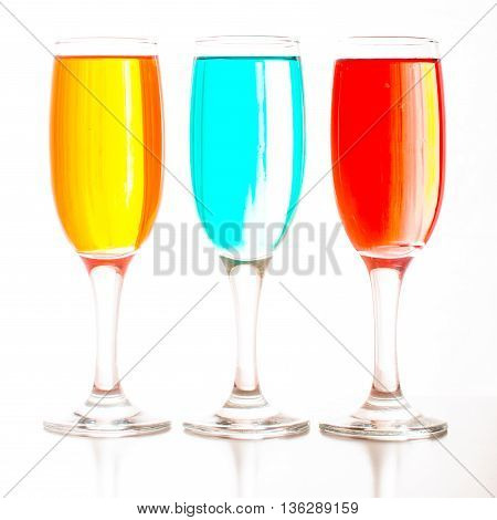 Glasses Of Champagne With Colored Liquids Standing In A Row