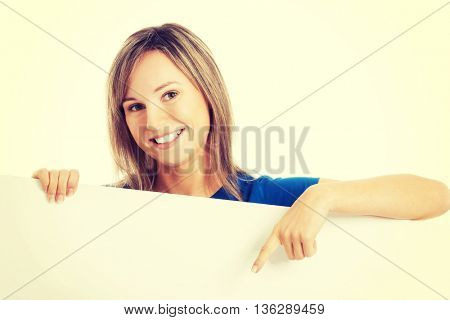 Casual beautiful woman pointing on copy space.