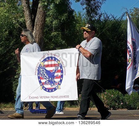 PHOENIX, AZ, USA - NOV. 11: Two male veterans holding a white banner with a blue eagle and red and white stripes that states, Madison Street Veterans Association- Ending Veteran Homelessness, marching in Veteran's Day Parade in Phoenix, Arizona on Novembe