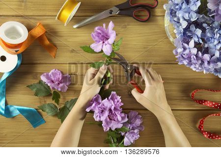 overhead of florist woman at work on table