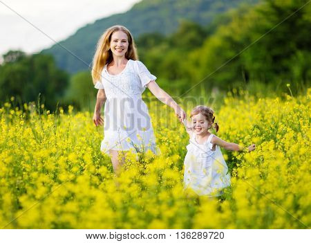 happy family mother and child girl little daughter playing and running on the meadow with yellow flowers