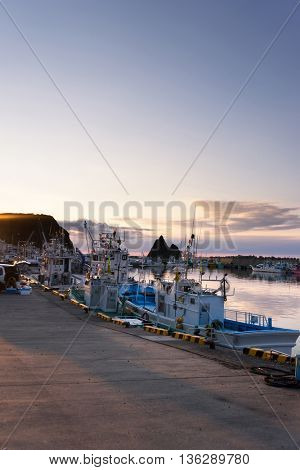 pier with crowded ships in japan hokkaido at sunrise