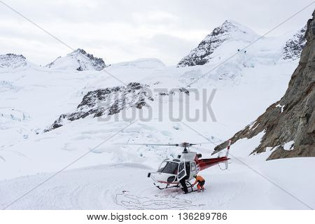 small red helicopter on alpes mountains