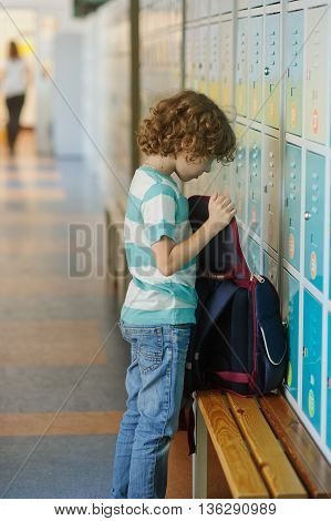 Little schoolboy standing near lockers in school hallway. He put the backpack on the bench and something it's looking for.