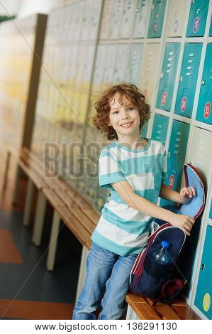 The primary school students standing in the hall near the lockers. The boy put the backpack on the bench and something shifts. He has a pretty face and curly blond hair.