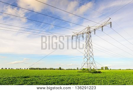 High voltage lines and pylons in a large Dutch potato field on a sunny day in the spring season with a slightly cloudy sky.
