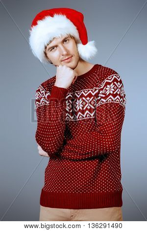 Portrait of a smiling young man in Santa Claus cap. Christmas celebration.