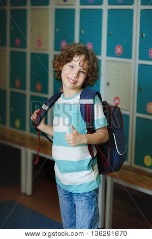 Elementary school student standing near lockers in school hallway. Behind kid's school backpack. The boy has blond curly hair and blue eyes. With a gesture he showed that he's all right.