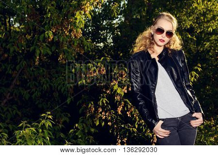 Modern young woman in leather jacket and sunglasses posing outdoor. Beauty, fashion. City style.