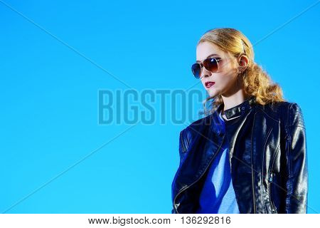 Modern young woman in leather jacket and sunglasses posing outdoor over blue sky. Beauty, fashion. Urban style.