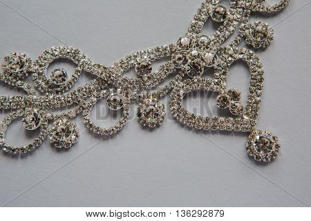 part of the jewelry made of precious transparent small stones framed in a silver heart with swirls and flowers on a white background