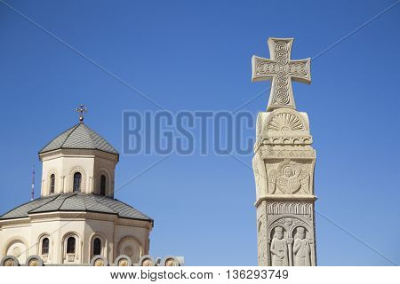 Stone column with christian cross on the top and carved portraits of angels and saints in front of Georgian church