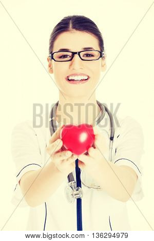 Beautiful young female doctor holding a heart.