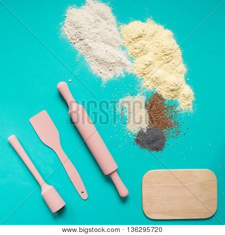Baking accessories kitchen utensils pink rolling pin spatulaboard and flour with colorful spices on a turquoise background