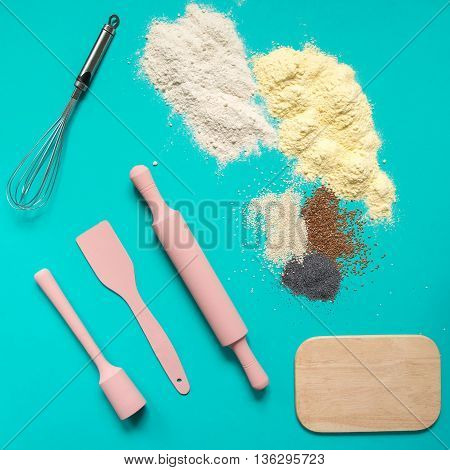 Baking accessories kitchen utensils pink rolling pin spatula board whisk for whipping and flour with colorful spices on a turquoise background.