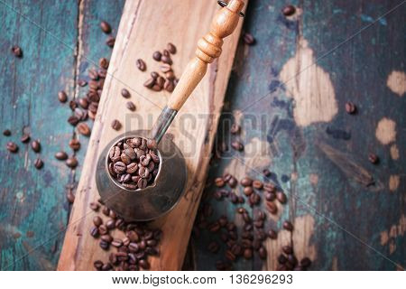 Roasted coffee beans in a cooper turk on a vintage background top view with copy space