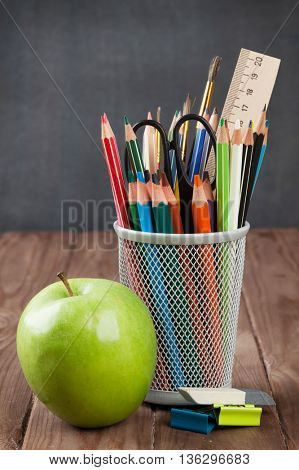 School and office supplies and apple on classroom table in front of blackboard