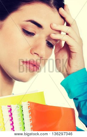 Portrait of young sad female student with workbook.