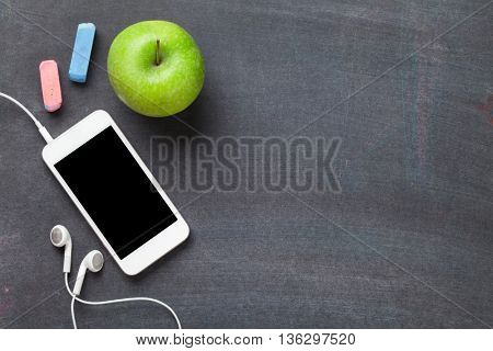 Smartphone and apple on blackboard background. Top view with copy space