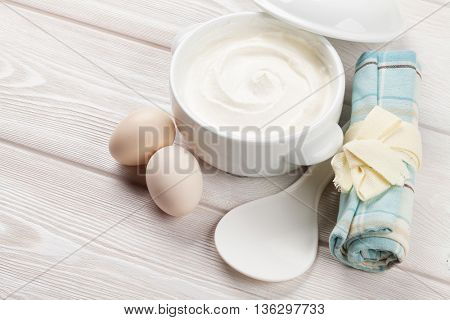Sour cream in a bowl and eggs on wooden table