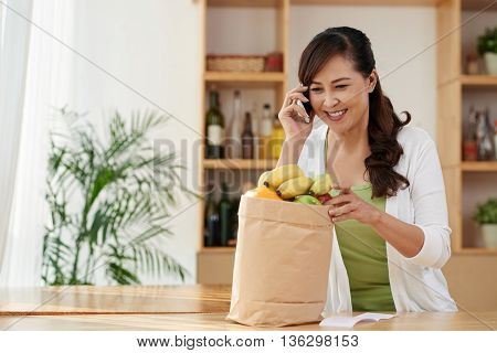 Cheerful Vietnamese woman with grocery bag calling on phone